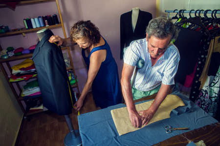 needlewoman: Mature couple working together on a tailoring Stock Photo