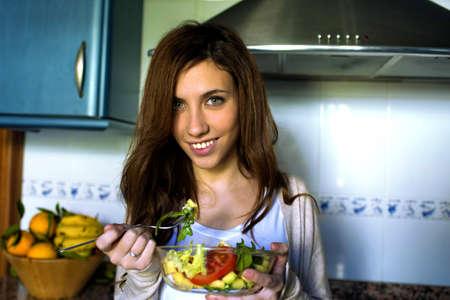 ojos verdes: Retrato de mujer joven con los ojos verdes comer ensalada. Foto de archivo