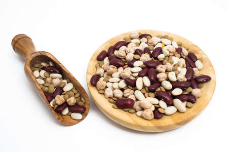 leguminosas: Legumes in wooden plate and scoop on white background.