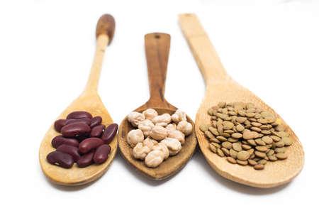 leguminosas: Las legumbres en cucharas de madera sobre fondo blanco.