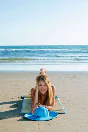 beach mat: Portrait of attractive blonde woman smiling at camera while lying on mat on beach