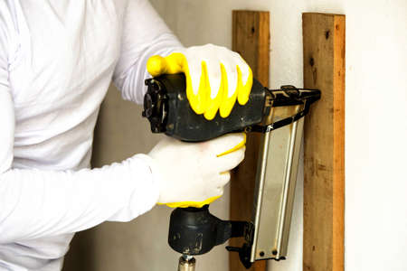home repairs: Man doing home repairs with electric stapler