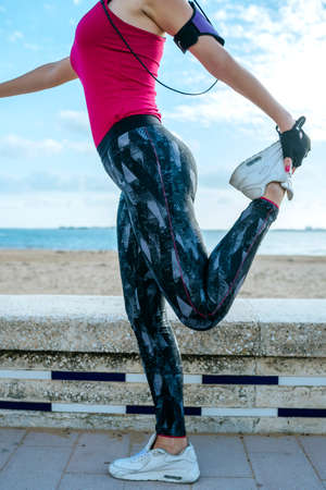 Woman doing leg stretching exercises on the beach