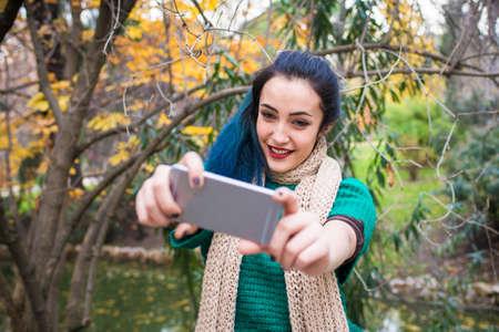 cola mujer: Mujer joven que toma una autofoto con smartphone