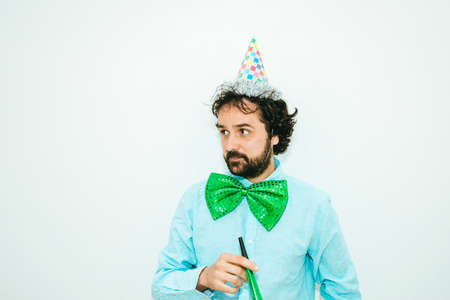 Portrait of Man with party hat, noisemakers and big green tie. Stock Photo