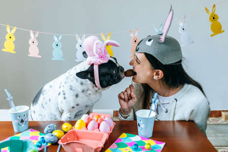 Woman and dog eating an Easter egg together Stock Photo