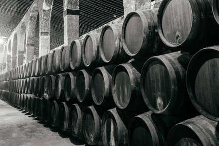 Botti per whisky o vino impilati in cantina in bianco e nero