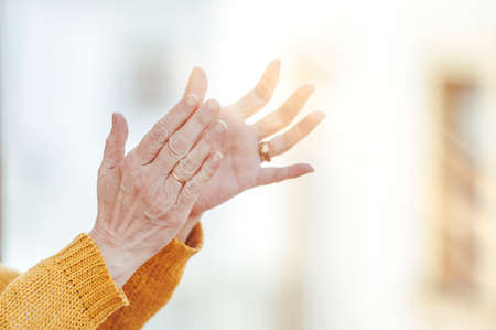 Close-up of hands clapping from the window