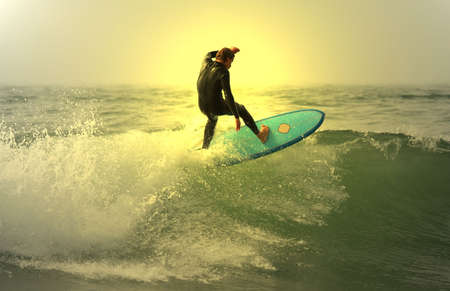 sunset surfer on top of the wave Stock Photo