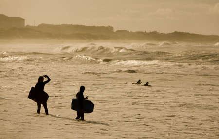 sunset bodybarders in the beach photo