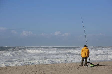 fisherman with yellow raincoat in the beach Stock Photo - 658245