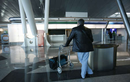 man and trolley waiting in the airport photo
