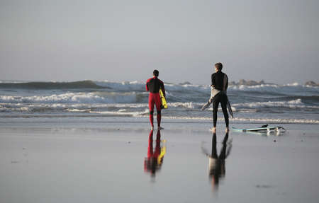 reflex of two surfer in the beach photo