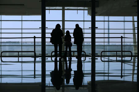 airport check in counter: family looking through the window in the airport