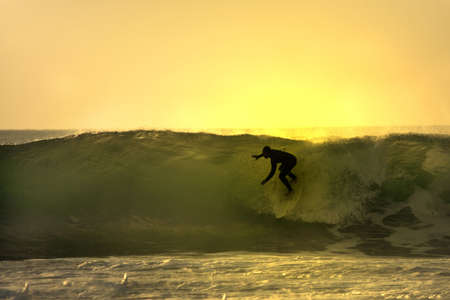 exhilaration: sunset surfer in the wave