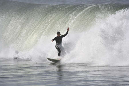 plucky: surfer with a big wave in the back