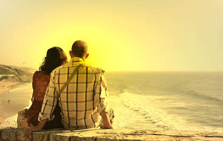 photo of a couple seated watch the sunset
