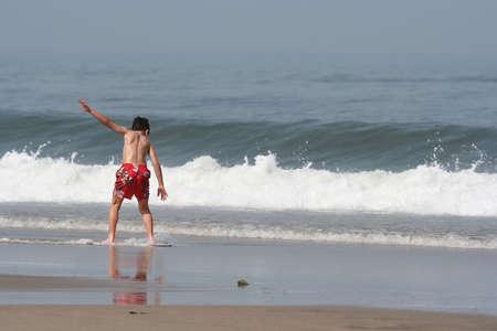 skimming: chico haciendo descremado en la l�nea de costa