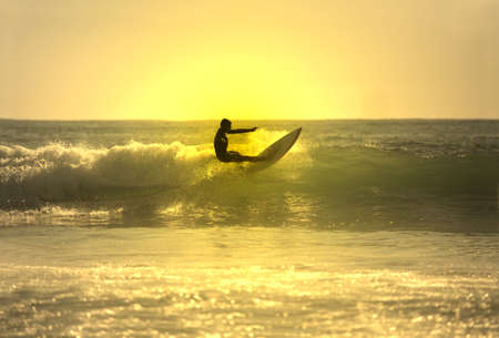 floater: surfer making a floater at sunset