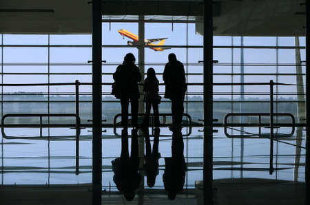 family looking to a airplane through the window in the airport photo