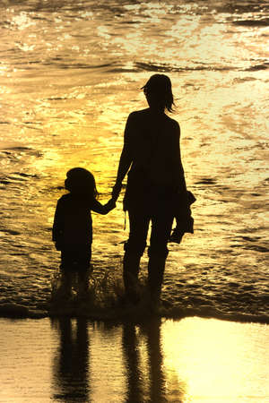 mother and son at sunset in the beach Stock Photo