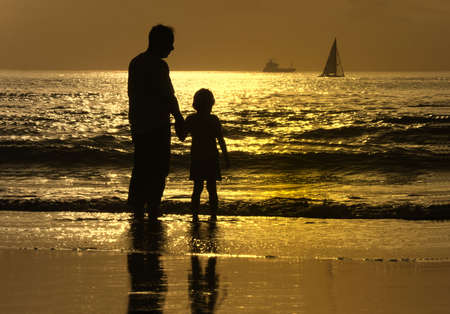 father and son at sunset in the beach photo