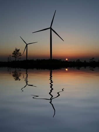 conservational: sunset Wind Turbines reflected in the water