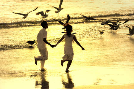 couple running in the beach with seagulls flying