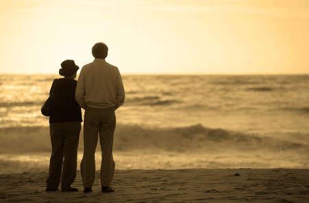 ancianos caminando: altos pareja mirando la puesta del sol