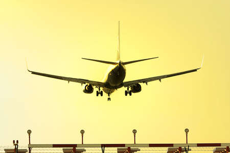photo of an aeroplane landing at sunset photo