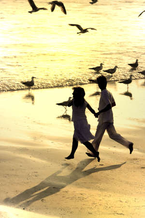 couple running in the beach with seagulls flying photo