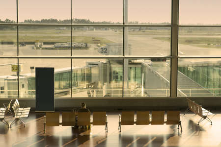 woman waiting in the airport at sunset photo