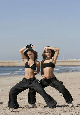 vivifying: twins training in the beach Stock Photo