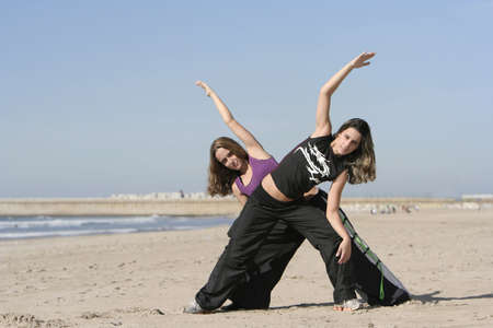 vivifying: twins working out in the beach