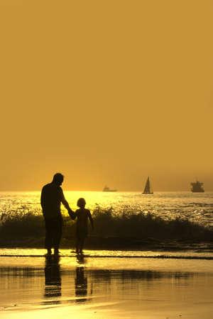 Vater und Sohn bei Sonnenuntergang am Strand Standard-Bild - 4596077