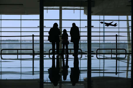 airport check in counter: family looking to an airplane through the window in the airport