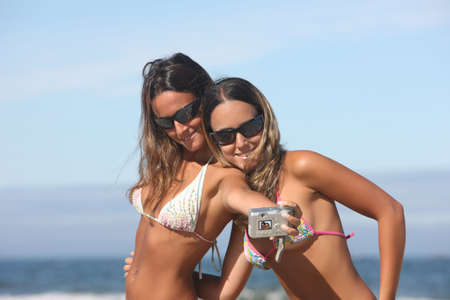 twins taking a photo of themselves on the beach photo