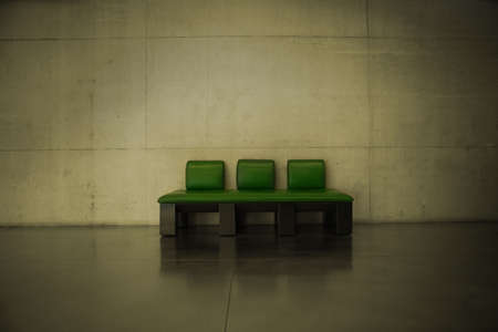 A green leather couch in a dark room