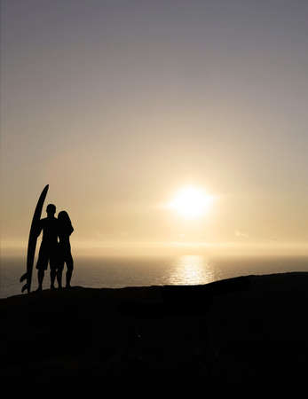 surf couple with a surf board at sunset photo
