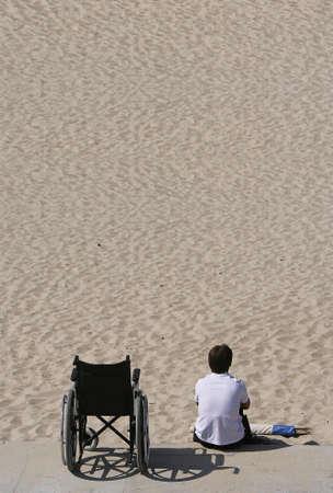 donna e la sedia a rotelle in spiaggia Archivio Fotografico