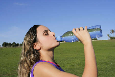 girl drinking water in the park photo