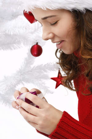 Beautiful young woman wearing santa hat next to christmas tree holding a christmas gift photo