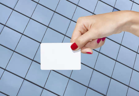 Hand holding an empty business card with glass building background Stock Photo - 8180110