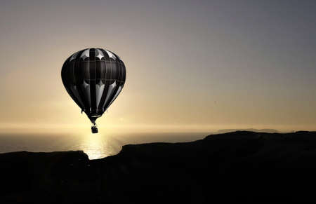 balloon flying into sunset over water photo