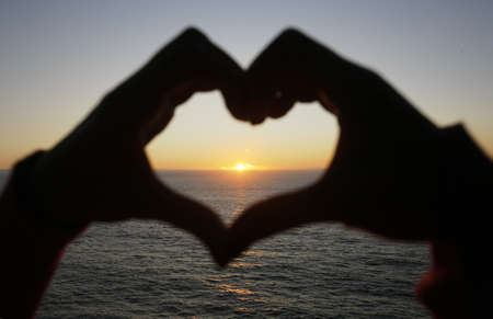 heart shape made with a girl hands at sunset - focus on the sun Stock Photo