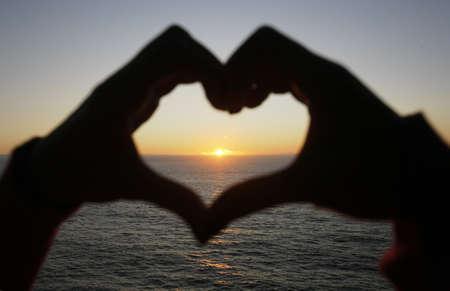 heart shape made with a girl hands at sunset - focus on the sun Standard-Bild
