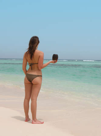 beautiful woman in a tropical beach holding a coconut photo