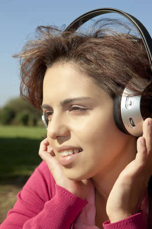 Pretty young girl listening music in the park Standard-Bild