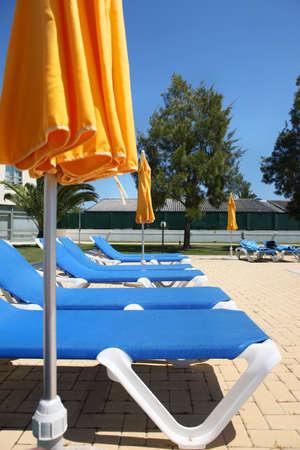 several sunbeds with yellow umbrellas Standard-Bild