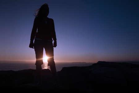 woman silhouette in th mountain at sunset  Stock Photo